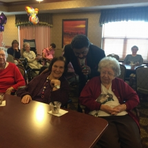 Birthday Party-Lilydale Senior Living-sneaking in to sing between two tenants